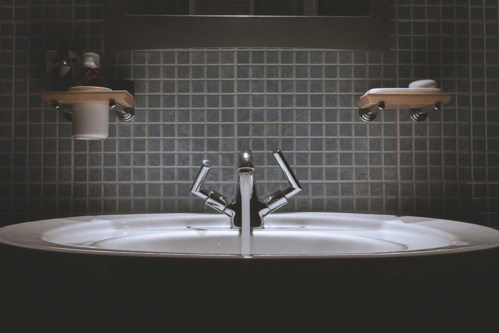 A dramatically lit bathroom faucet with the water running