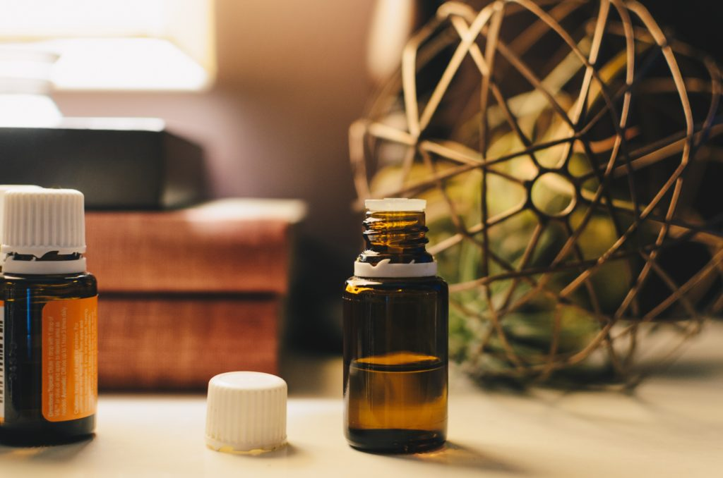 Two bottles of essential oils set against a warm, blurry background