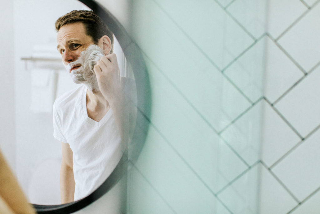 A man applying shave soap with a shave brush in a round mirror