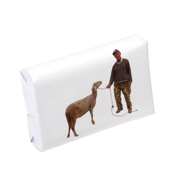 A white bar of Take Away Porto Soap featuring a wrapper with a picture of a man & a sheep