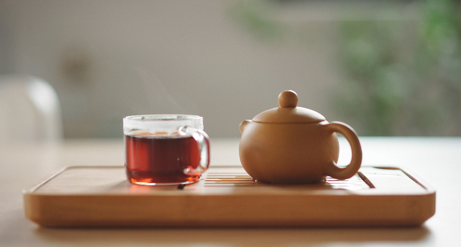 Image of Red Tea in Clear Glass with Ceramic Tea Pot