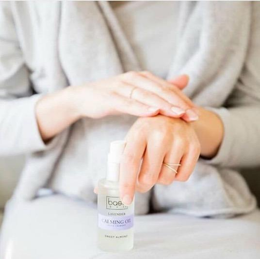 pregnant woman using lavender calming oil on hands