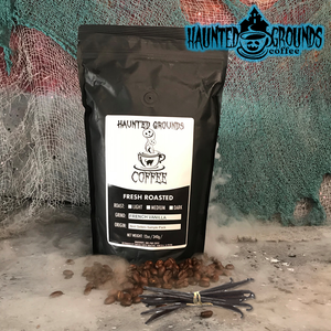 Vanilla beans and coffee beans in front of a Haunted Grounds Coffee pouch.