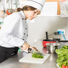 Chef in a kitchen slicing salad