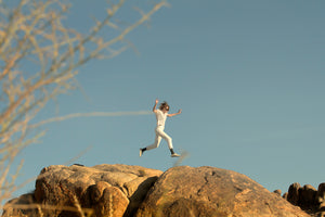 Photo of person jumping over rocks.