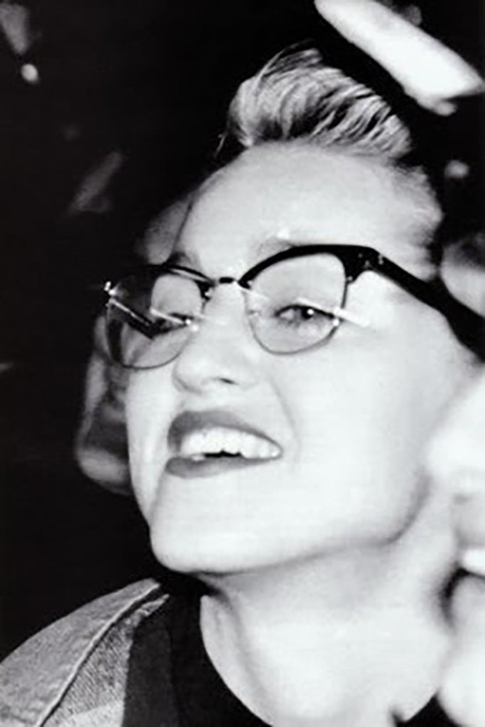 Black and white photo of Madonna wearing browline eyeglasses