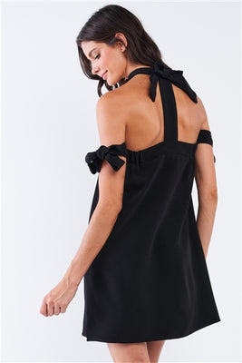 Charmed & Fortunate model wearing ladies' apparel black bow tie, T-silhouette, back-tie ribbon mini-tube dress.