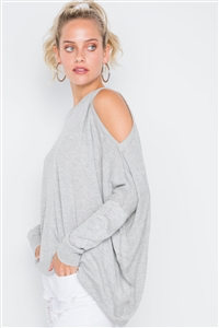 Charmed & Fortunate model wearing ladies' apparel heather grey asymmetrical, cold-shoulder sweater with a scoop neck, the left shoulder cut out, and an asymmetrical hem.