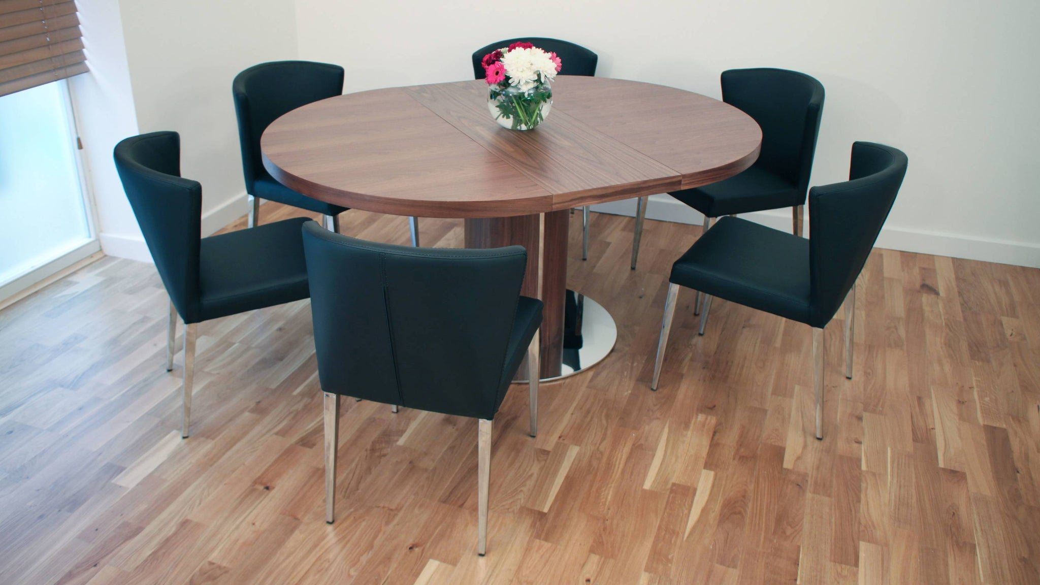 Large Round Walnut Extending Dining Table and Black Chairs