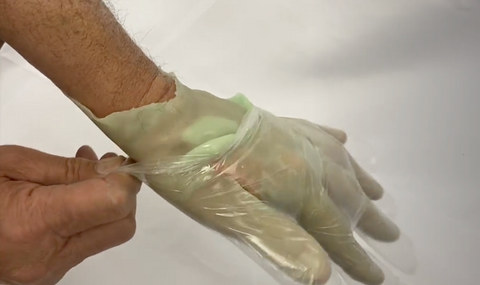 Putting a disposable glove over paraffin wax hand to lock in heat