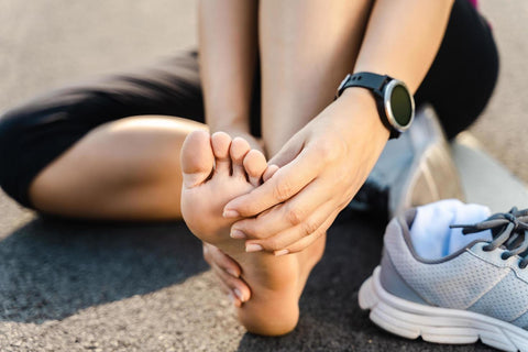 Runner holding foot post workout