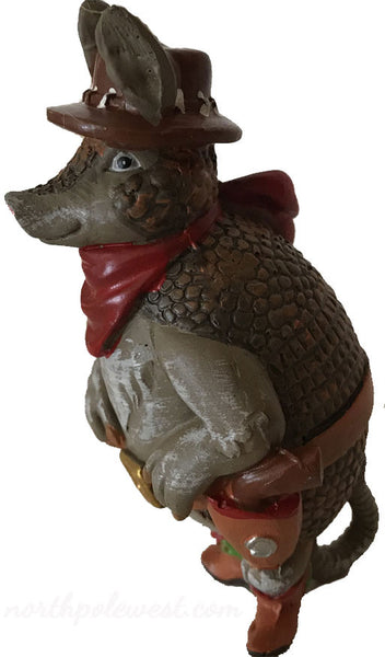 side view of standing armadillo with cowboy boots, hat,bandana and holster country western cowboy Christmas ornament from North Pole West
