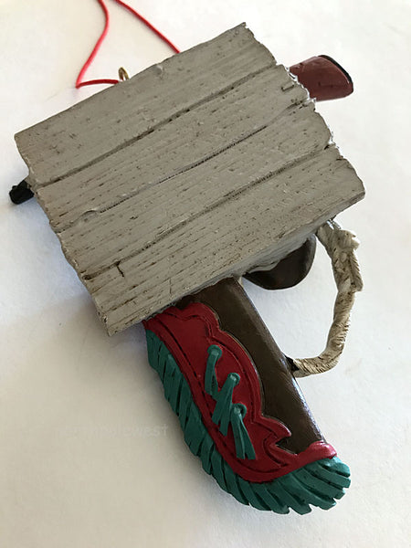 "Reverse side of cowboy Christmas ornament with cowboy hat,lasso chaps and rifle on wood-look sign that reads ""when life gets tough, cowboy up-from North Pole West"