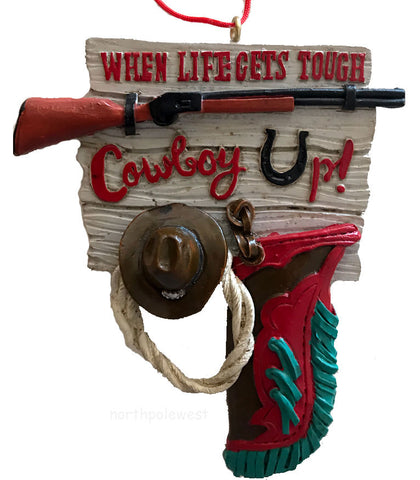 "Cowboy Christmas ornament with cowboy hat,lasso chaps and rifle on wood-look sign that reads ""when life gets tough, cowboy up-from North Pole West"