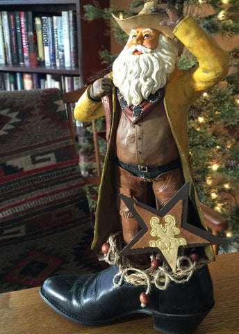 One of a kind Cowboy Santa tucked inside an old cowboy boot. He holds a saddle and has 3 stars.  With his duster open and his upward glance, he gives the imperssion he is searching the sky on a cold December night and so he is called the Star Rancher.