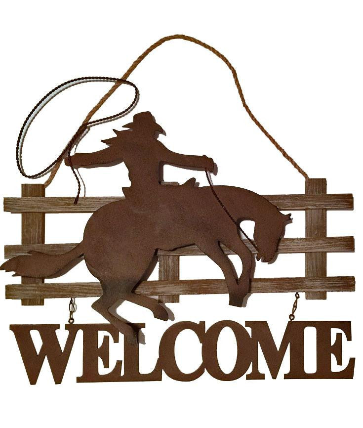 cowboy on horse by fence western welcome sign