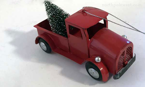 top view -Cowboy country Christmas ornament  vintage style tin red pick-up truck with Christmas tree from North Pole West