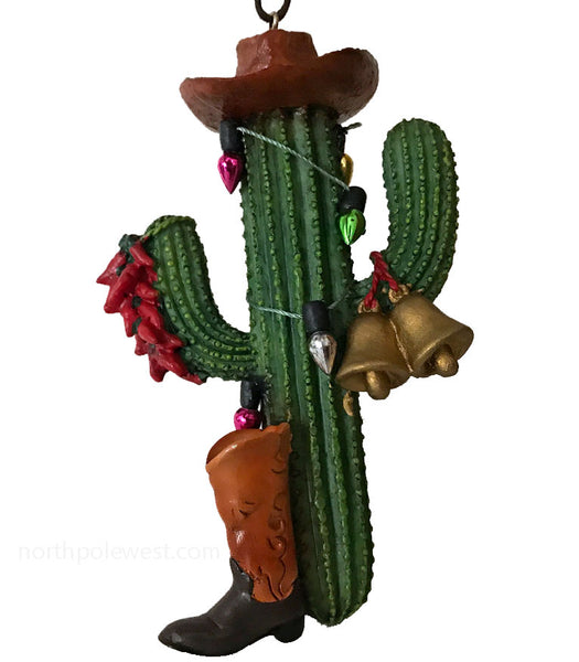 Saguaro cactus Christmas ornament with cowboy hat and boot decorated with mini lights and has chili peppers and bells - from North Pole West