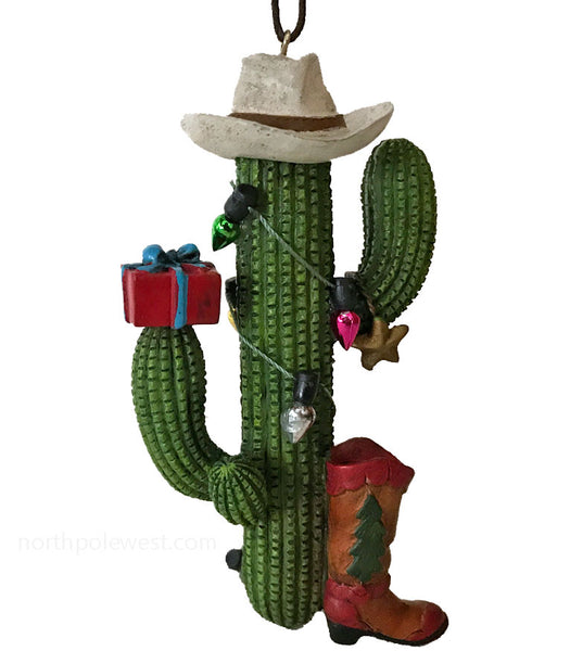 Saguaro cactus Christmas ornament with cowboy hat and boot decorated with mini lights and has a wrapped gift- from North Pole West