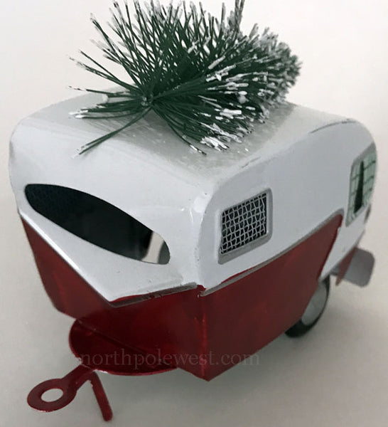 Side view of Tin camper trailer with Christmas tree on top Christmas ornament from North Pole West