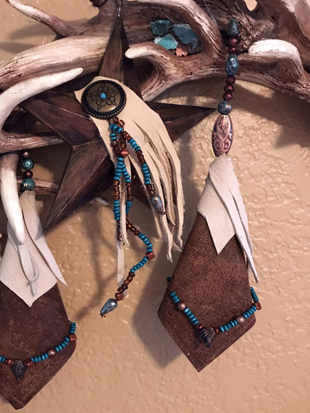 Close up view of Unique western antler style wreath with turquoise and copper pieces and rusty stars an dangles