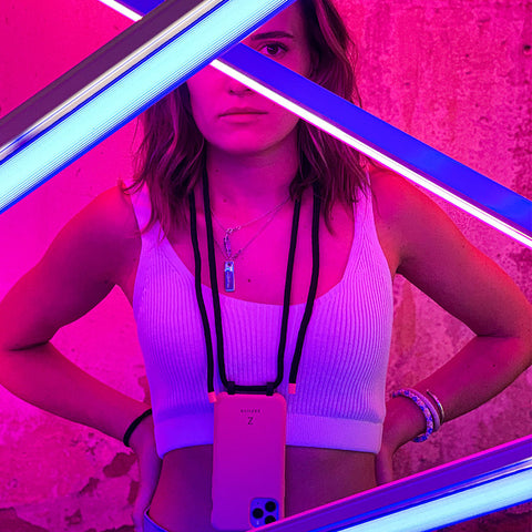 girl posing behind neon industrial lights wearing a Zaphyr phone case around her neck