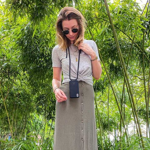 Girl wearing a Zaphyr phone chain/ phone case around her neck in front of bushes