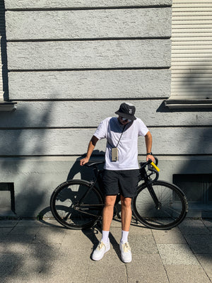 Boy photographed with grey Zaphyr case leaning on bike in front of building