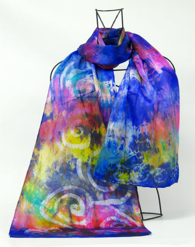 A luxury silk satin scarf in vibrant shades of bright violet golden yellows, pinks and rainbow flashes throughout a very versatile scarf