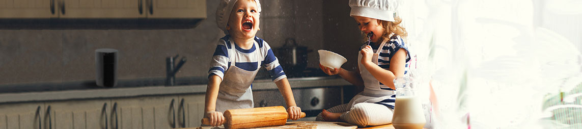 Two children baking in a kitchen. With tightvac TV4  and rolling pins.