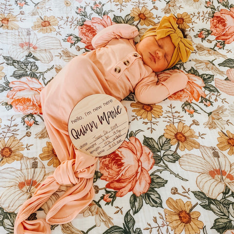 Baby girl wearing a first day bundle with a birth announcement sign, knotted gown and a swaddle blanket