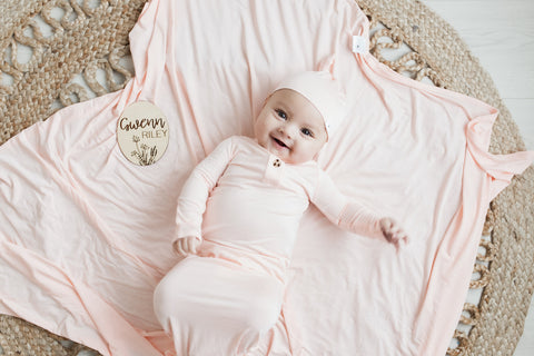 Baby girl wearing a first day bundle with a birth announcement sign, knotted gown and hat, and a swaddle blanket