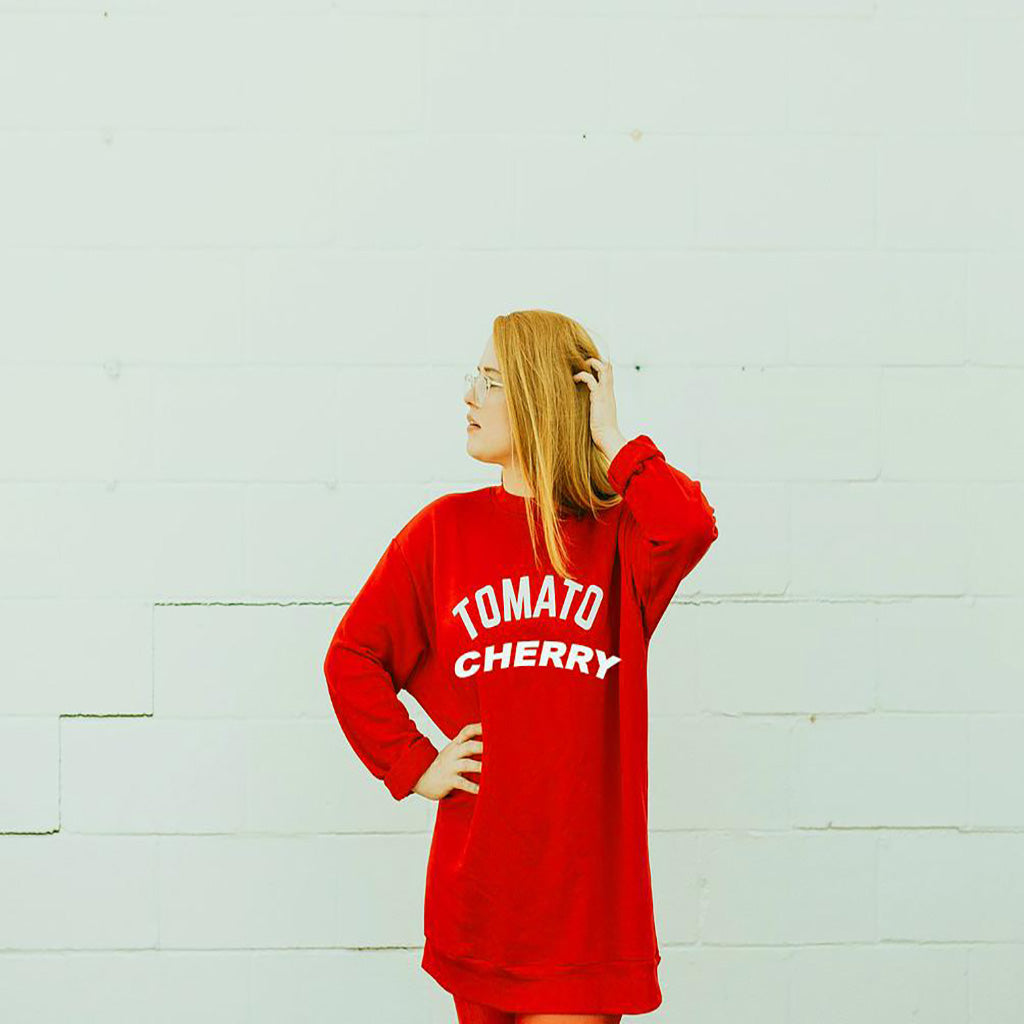 Girl with a orange/red sweat sweater against white wall