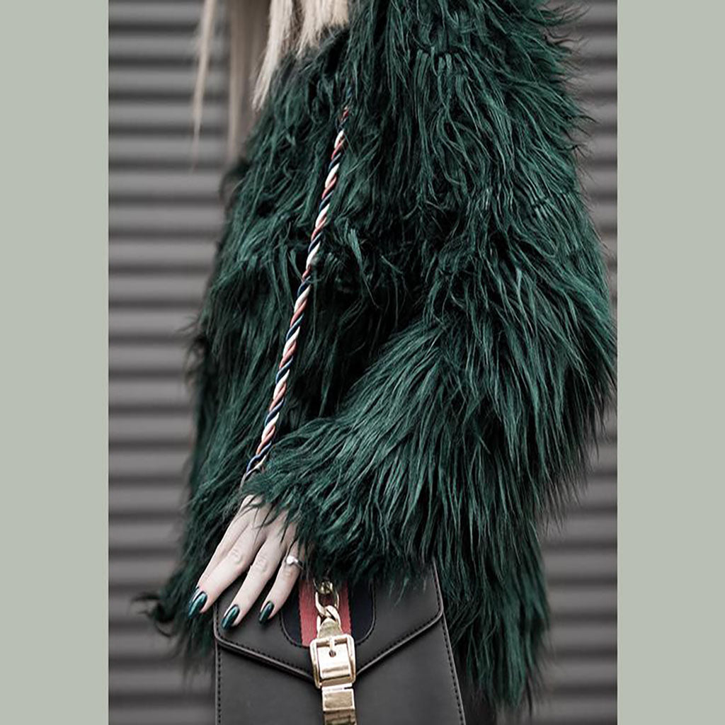 Woman wearing a green furry coat with a black bag