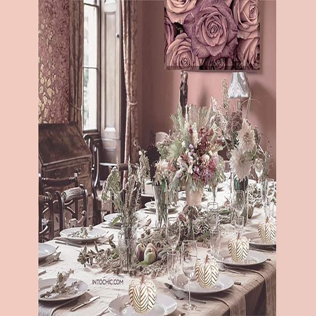 Holiday thanksgiving table. Ideas for a prepared set dinner for the holidays. Elegant and chic table seating. Floral center pieces, Nice home decor, wall roses frame, and white pumpkin decor table.