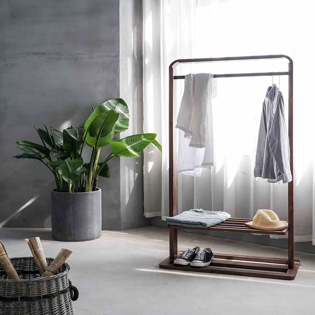 Room with a wooden portable hanger for clothes and shoes. On the left hand has a big grey plant pot, next to it a a window with white shimmer curtains. In front of the window is the portable hanger.