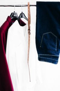 Two blouses one burgundy and the other white color, hanging on a portable hanger. Also there is a brown belt and a pair of jeans.