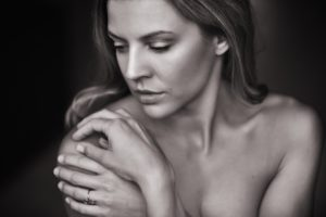 Women in her thirties. Close up on her face and upper body. She is touching her right shoulder gently. She has long hair. Photo in white and black. She is not wearing clothes