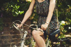 Woman in a floral dark dress with a cross body black small bag riding a bike.