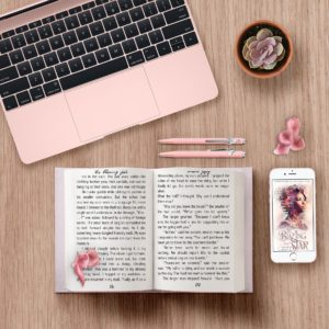 Wooden desk whit a pink open laptop , open book, two pink pens and a cellphone next to each other,