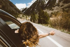Women seating in a passenger seat , her head and arm outside of the road enjoying the view and wind, she is in a road trip. The scenery are the mountains