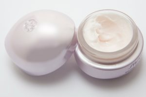 Round shape bottle of cream. All tones in white and pearl. The cream bottle is open