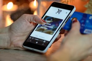 the picture shows the hand of a woman using her cellphone for a online shopping and in her other hand has a credit card