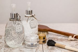 Clean face products. Two glass bottles. two face creams , a hair brush and blush brush