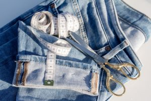 Pair of jean folded and on top of it there is a white tape measure and one sicissors