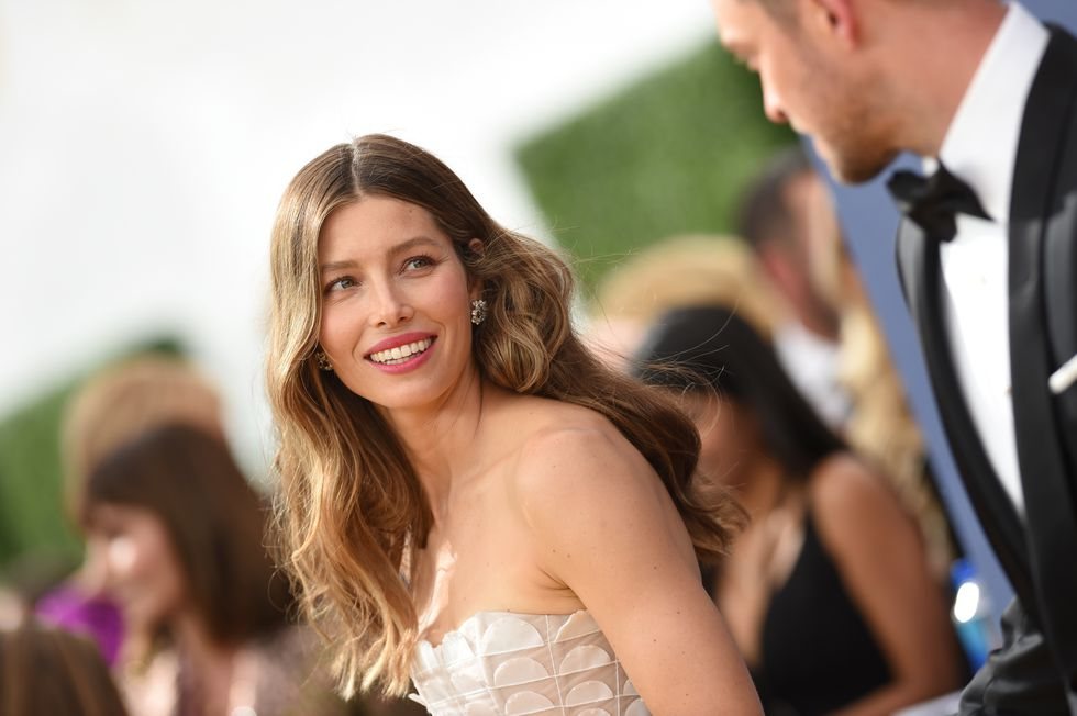 Jessica Biel is wearing a white strapless with cascading ruffles gown by Ralph & Russos, Harry Winston Jewelry and Tyler Ellis Clutch