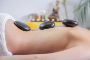Woman on a spa. She is laying down on her tummy and has three black stones.