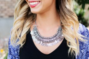 bloom women wearing a metal necklace and a v neckline black blouse
