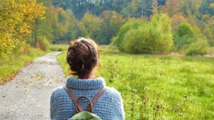 Woman walking on a trail, she is looking the trees and grass wearing a blue sweater and green backpack