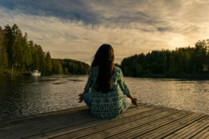 Woman wearing comfortable clothes seating on a pier in from tof a lake and trees, she is meditating at sunset